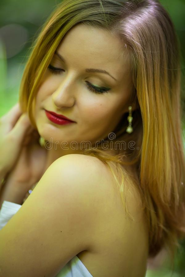 Close up Portrait of romantic blonde woman in white dress in fairy forest, selective focus stock photo