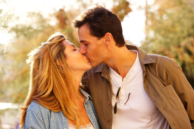 Close up romantic couple outside kissing on date stock photo