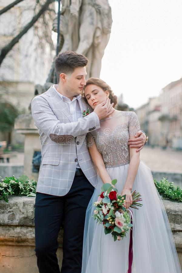 Close-up portrait of romantic young wedding couple embracing each other while standing on the old stone stairs in city stock photos
