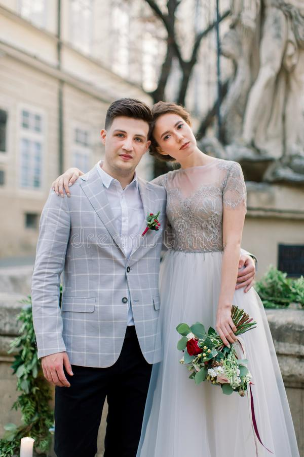 Close-up portrait of romantic young wedding couple embracing each other while standing on the old stone stairs in city stock photography