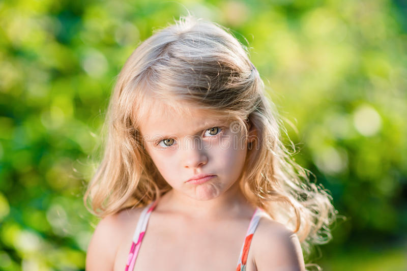 Close-up portrait of sad blond little girl with pursed lips. Sunny summer day in beautiful park stock image