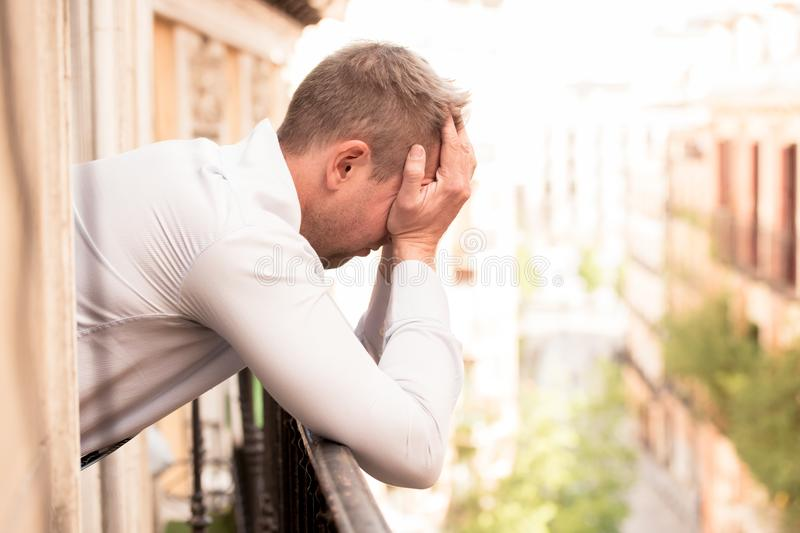 Sad depressed man feeling low and sad in mental health concept. Close up portrait of sad and depressed man looking out the window on a balcony at home suffering stock photos
