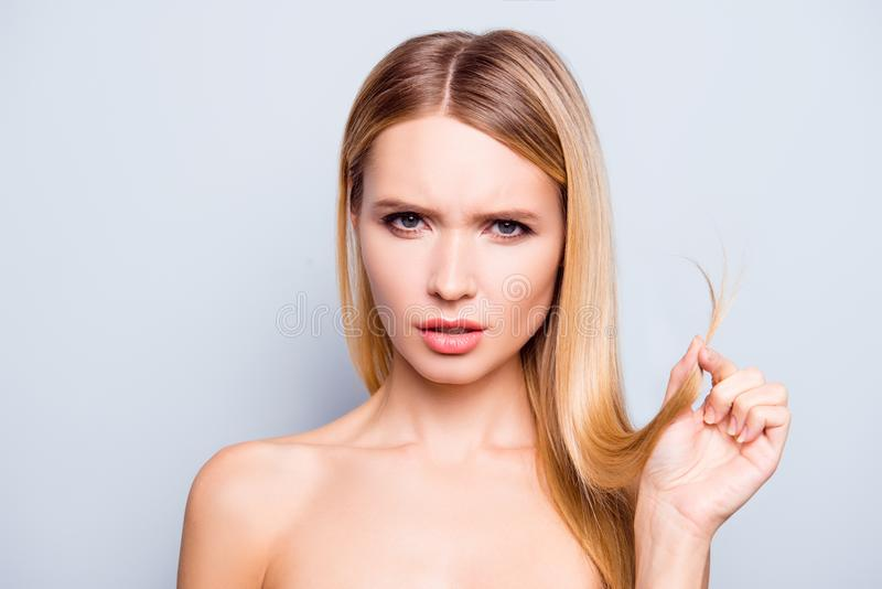 Close up portrait of sad and frustrated young woman showing split ends of her blonde hair. She is isolated on grey background royalty free stock photos