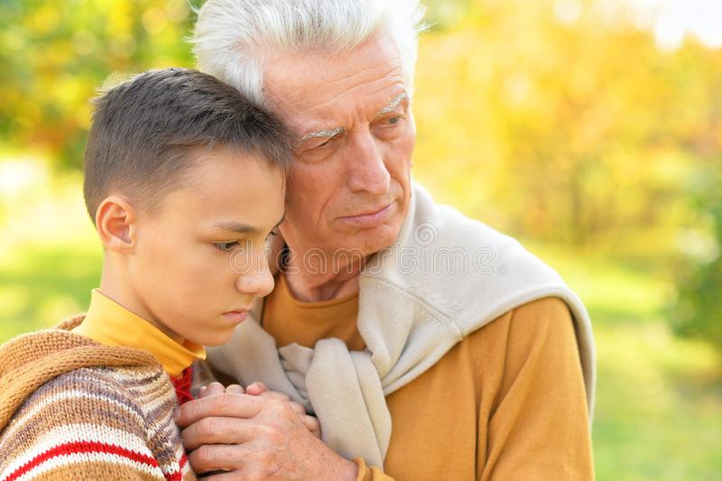 Close up portrait of sad grandfather and grandson hugging royalty free stock photo