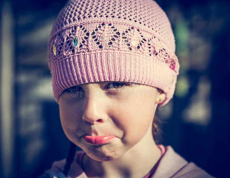 Close-up portrait of sad little girl with pursed lips. Photos in retro style stock images