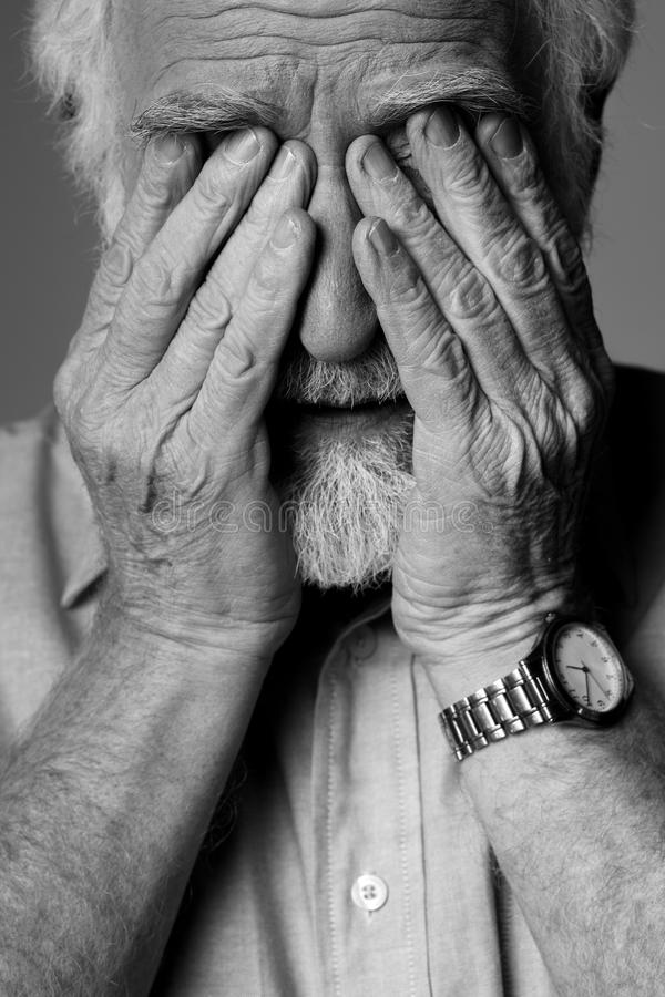 Old sorrow man with hands to his eyes royalty free stock photo
