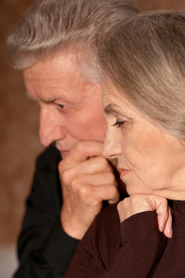 Close up portrait of sad senior couple posing at home royalty free stock images