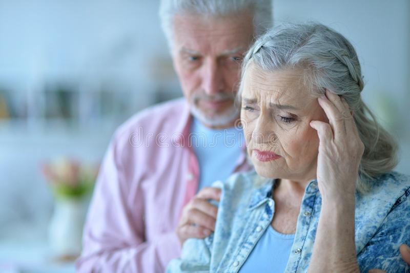 Close up portrait of sad senior couple posing stock photography