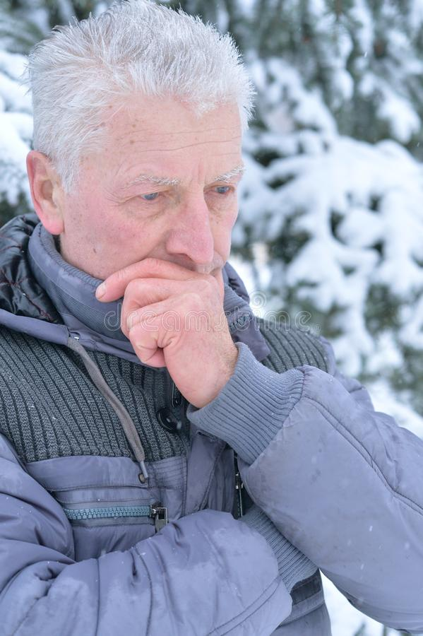Close up portrait of sad senior man standing outdoors in winter royalty free stock images