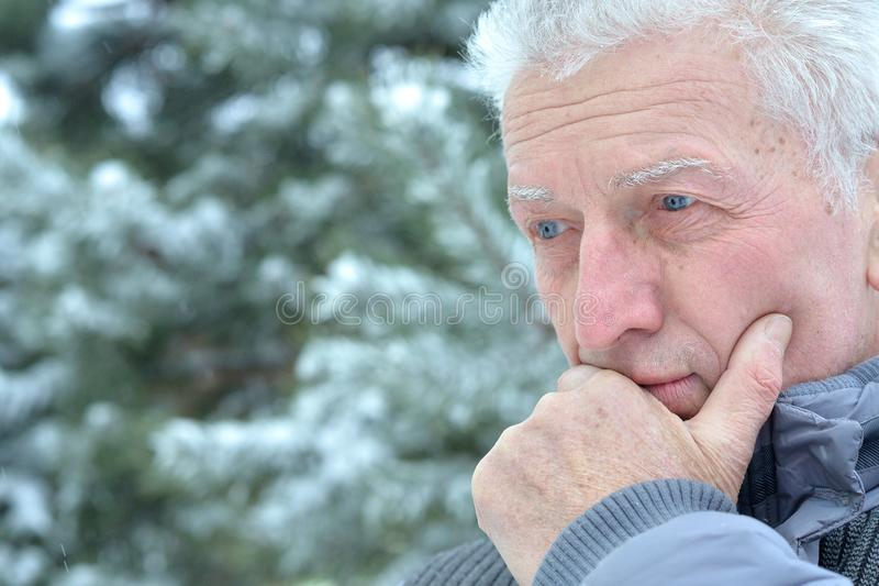 Close up portrait of sad senior man standing outdoors in winter stock photography