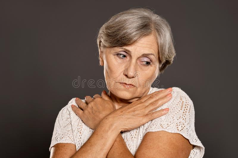 Close up portrait of sad senior woman on a gray background royalty free stock photo