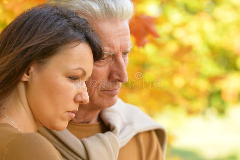 Close up portrait of sad woman and senior man hugging stock photography