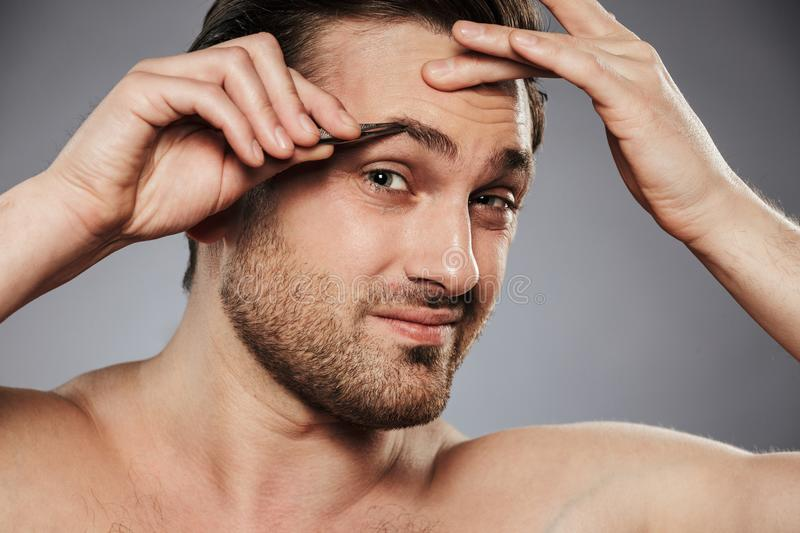 Close up portrait of a scared shirtless man plucking eyebrows royalty free stock photography