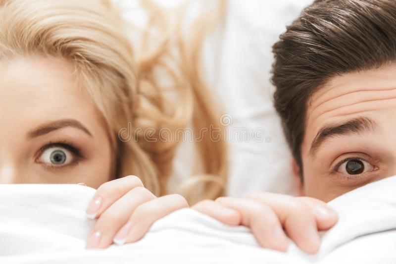 Close up portrait of a scared young couple. Looking at camera while lying under the blanket in bed royalty free stock image