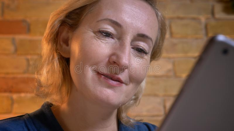 Close-up portrait of senior caucasian lady working attentively and gladly with tablet in cozy home atmosphere. stock photo