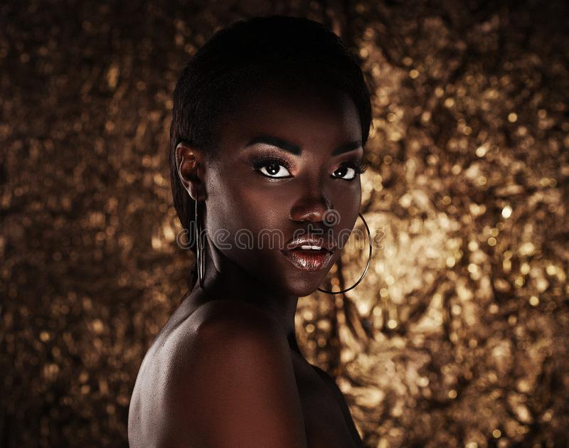 Portrait of sensual young african woman against golden background royalty free stock photography