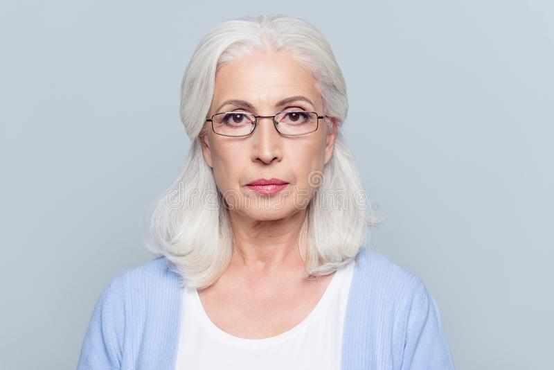 Close up portrait of serious, aged, charming woman in glasses over grey background stock photos