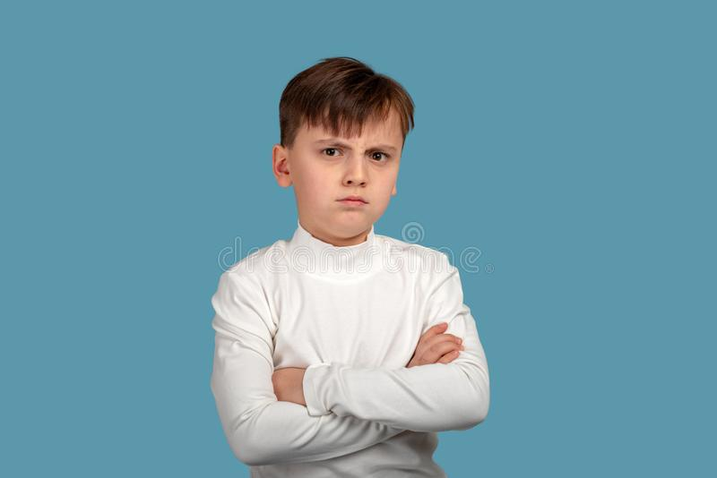 Studio shot of a serious or angry boy wearing white shirt with arms crossed on blue background. Close up portrait of a serious or angry boy wearing white shirt stock photo