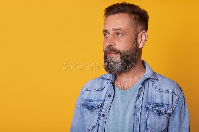 Close up portrait of serious attentive man looking aside, being calm and pensive, wearing casual jeans jacket and blue t shirt, royalty free stock photo