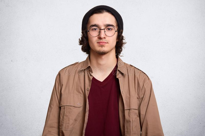 Close up portrait of serious man with curly hair, wearing maroon shirt, brown jacket, black cap and rounded spectacles, looking stock photography