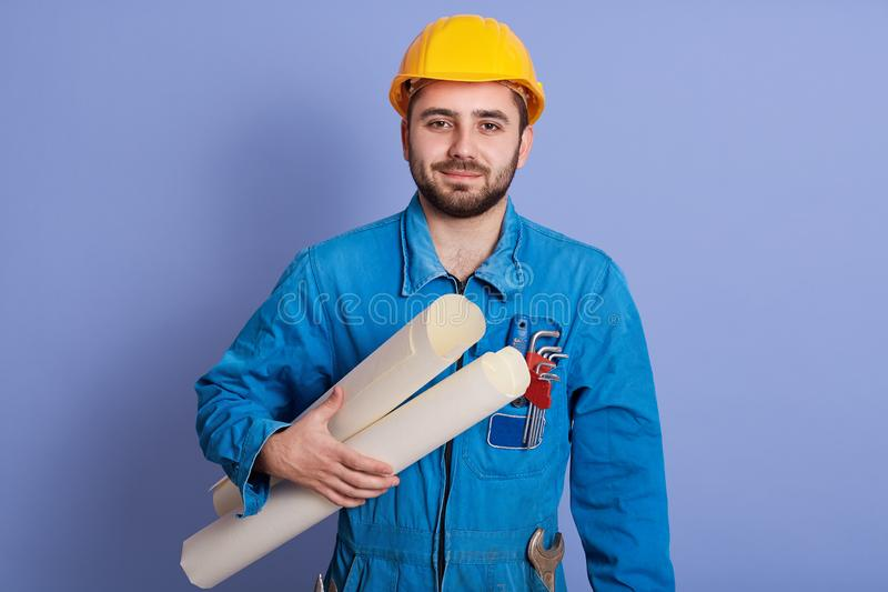 Close up portrait of serious man wearing uniform and helmet, attractive architect considers drawings isolated over blue background stock image