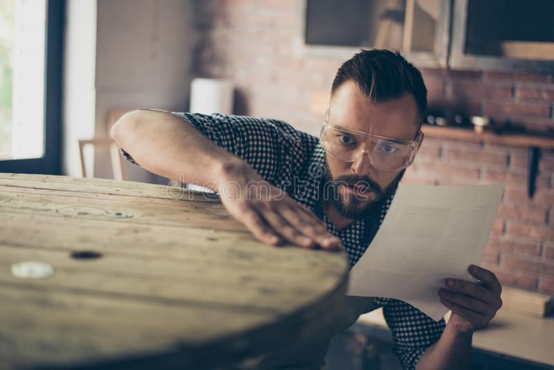 Close up portrait of serious minded hardworking craftsman wearing safety protective glasses and work clothes, he is verifying and royalty free stock image
