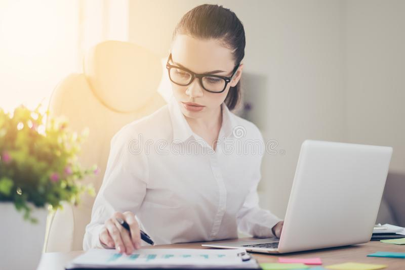 Close up portrait of serious young business lady economist in formal wear and with glasses, pony ail, concentrated on paper work stock photography