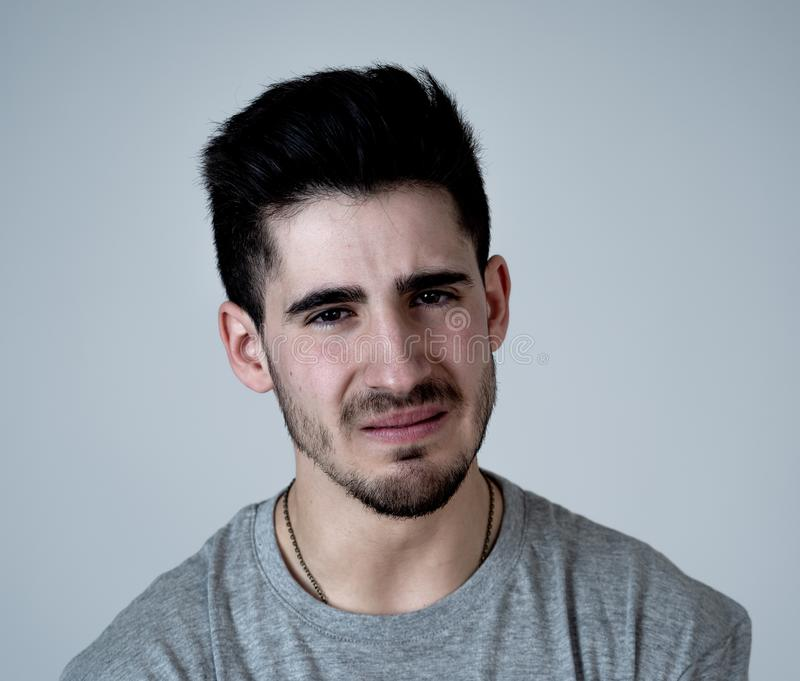 Human expressions and emotions. Portrait of young attractive sad and depressed man. Close up portrait of sexy young man looking sad and stressed crying and stock photography