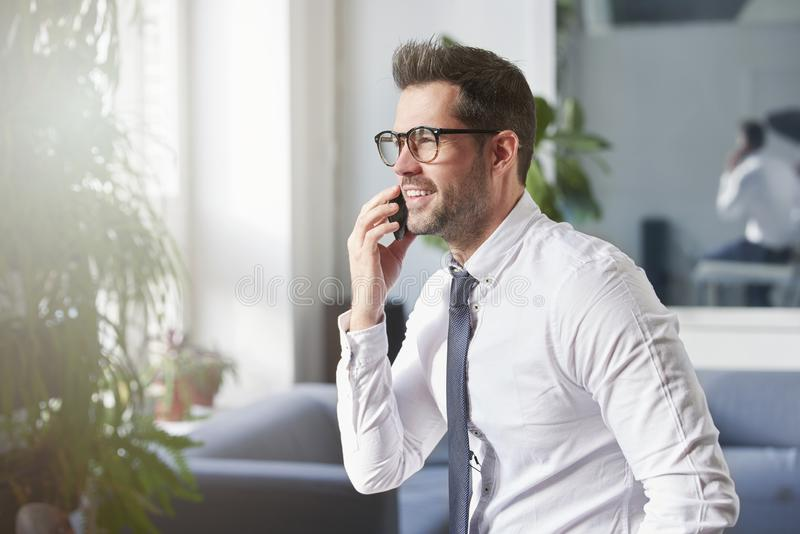Businessman making a call while sitting in the office royalty free stock photo