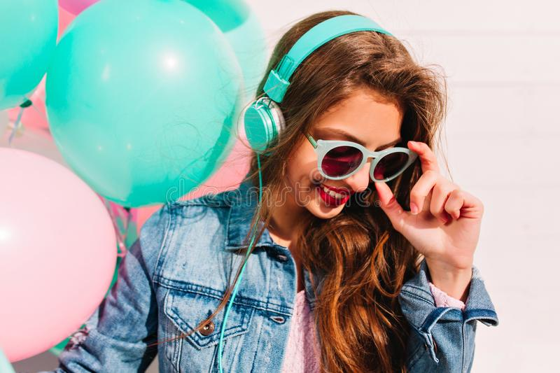 Close-up portrait of shy birthday girl testing new turquoise headphones received as a gift. Attractive brunette young. Woman having fun at the party and enjoys stock photo