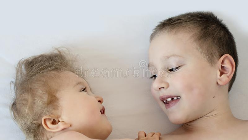 Close-up portrait of siblings lying on bed. Boy loves his disabled younger brother. - image royalty free stock image