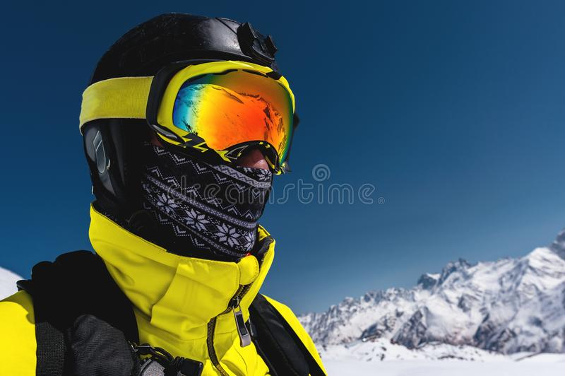 Close-up portrait of a skier in a mask and helmet with a closed face against a background of snow-capped mountains and royalty free stock photos