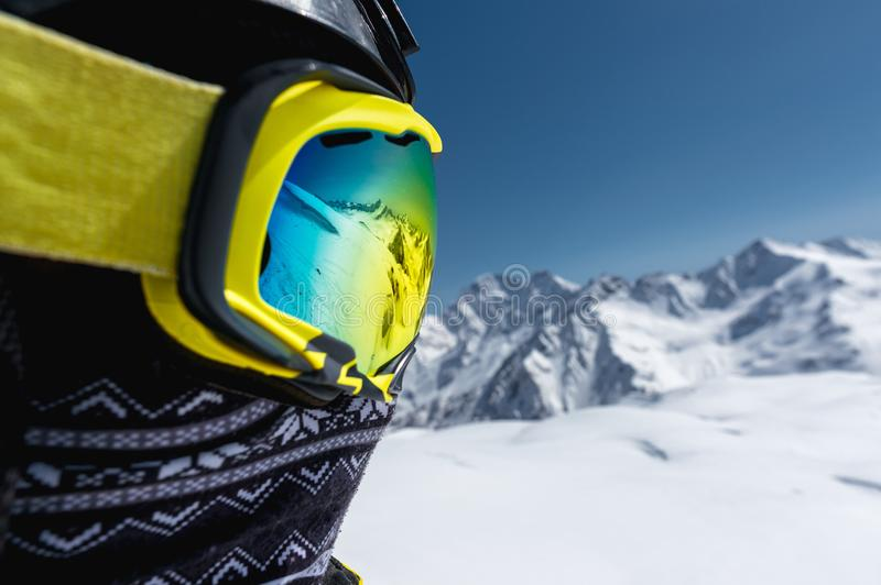 Close-up portrait of a skier in a mask and helmet with a closed face against a background of snow-capped mountains and stock photography