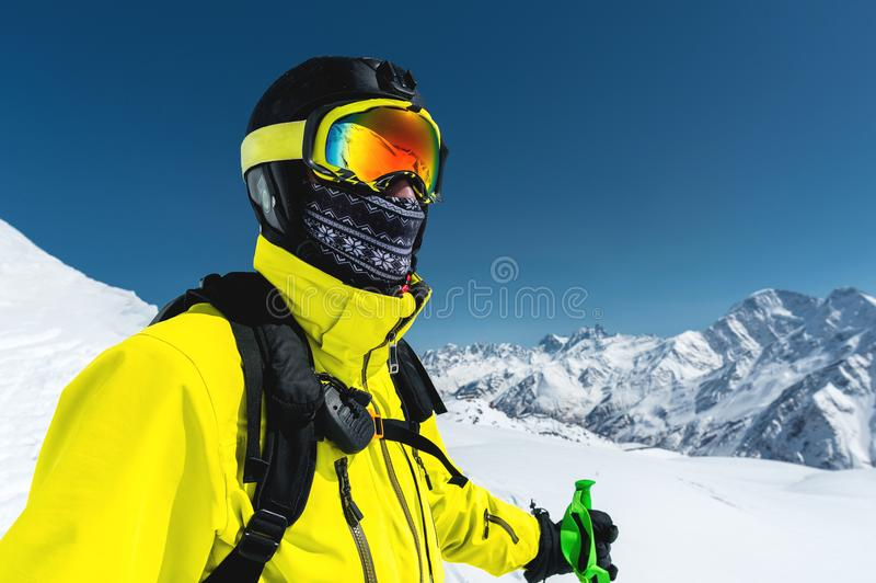 Close-up portrait of a skier in a mask and helmet with a closed face against a background of snow-capped mountains and stock photos