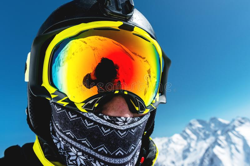 Close-up portrait of a skier in a mask and helmet with a closed face against a background of snow-capped mountains and stock image