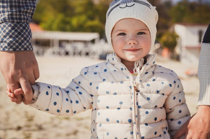 Close up portrait of small smiling kid holding father`s and mother`s hands outside at the beach stock images