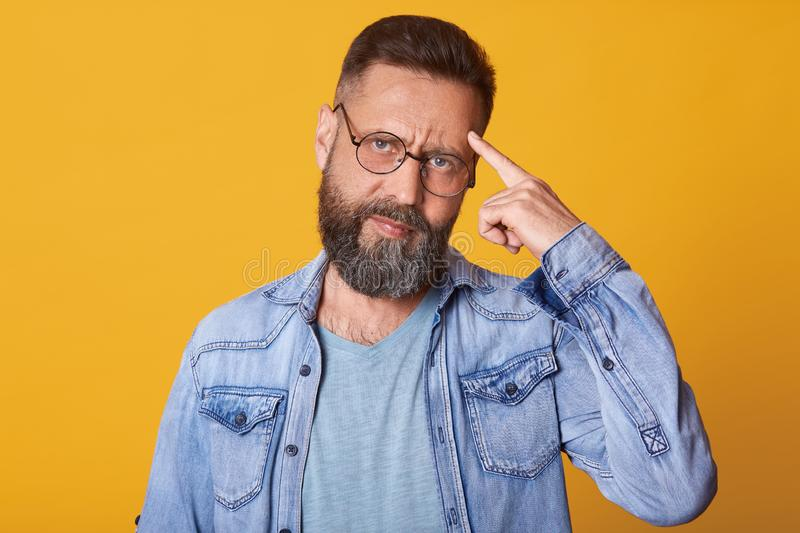 Close up portrait of smart handsome middle aged Caucasian man thinks with finger on head  on yellow background, wears royalty free stock photography