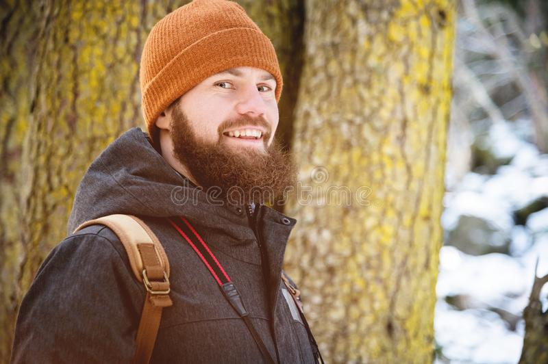 Close-up portrait of a smiling bearded young man in a hat and a backpack in a coniferous forest royalty free stock photos