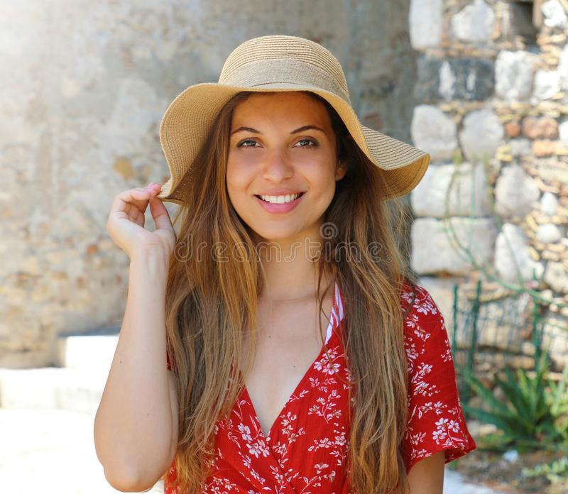 Close up portrait of smiling beautiful woman with red dress and hat outdoors royalty free stock photos