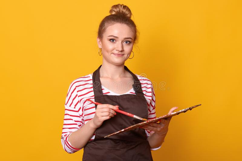 Close up portrait of smiling blonde artist girl with palette of colour in art studio, attractive young female wearing striped stock photo