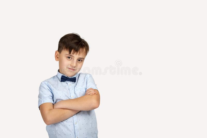 Studio shot of a smiling boy wearing a blue shirt and bow tie with arms crossed on grey background. Close up portrait of a smiling boy wearing a blue shirt and stock photo