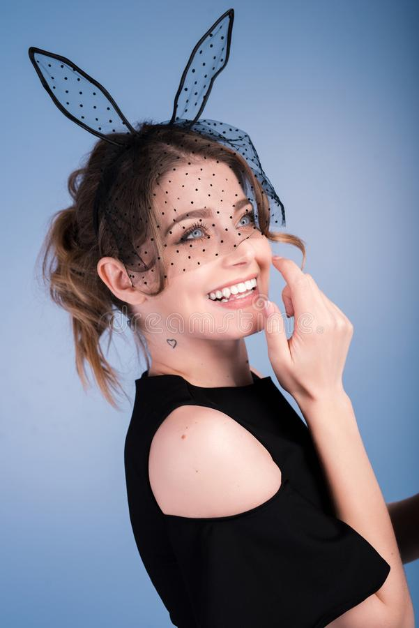Close up portrait of a smiling brunette young woman with bunny ears stock photography