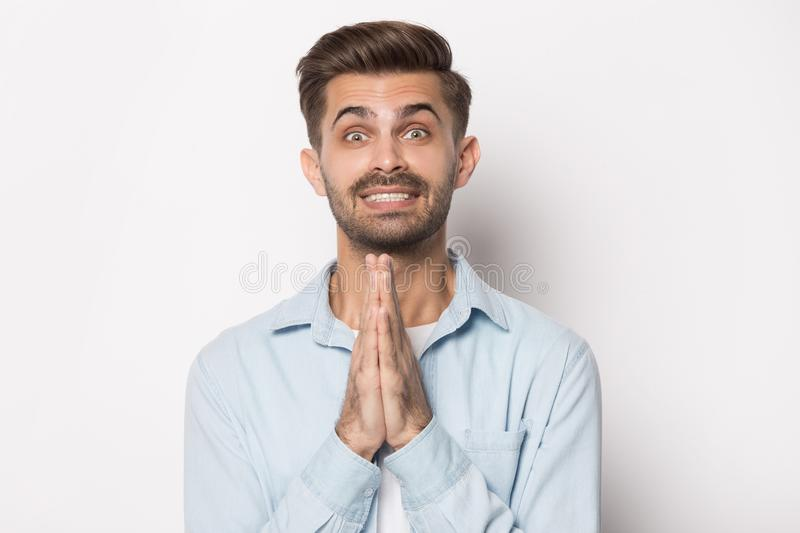 Close up portrait with smiling cunning bearded man begs. Close up head shot image of happy smiling cunning bearded man begs and holding folded hands as sign of royalty free stock image