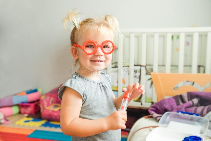 Close up portrait of smiling cute blondy toddler baby girl playing doctor with plastic toy glasses and syringe at home, in child r stock photo