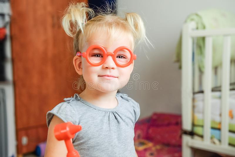 Close up portrait of smiling cute blondy toddler baby girl playing doctor with toy glasses and otolaryngologist instruments at hom royalty free stock photos