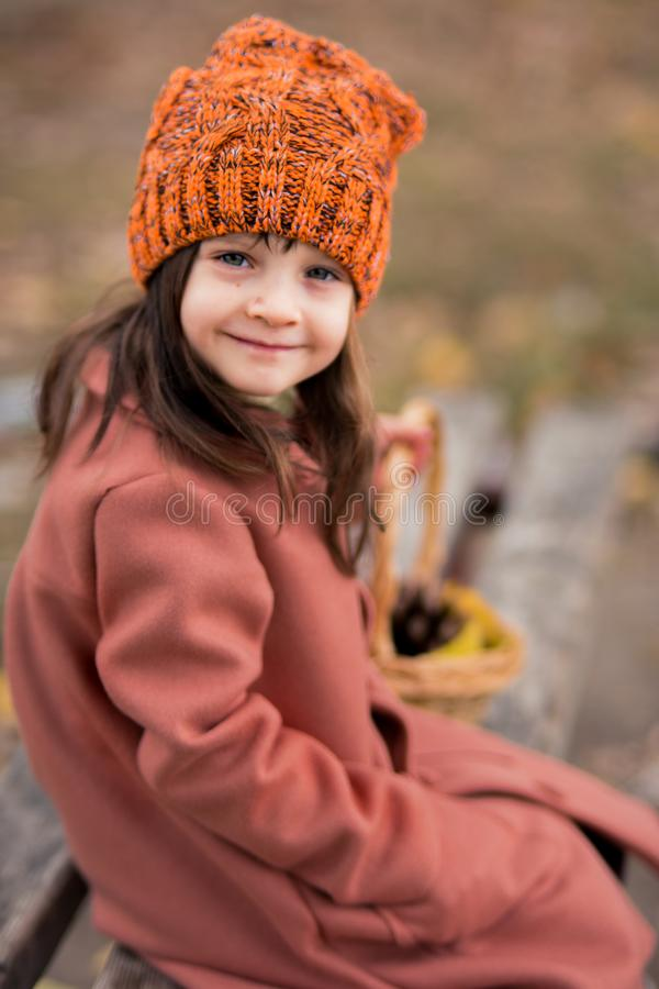 Close-up portrait of a smiling girl in a brown coat and an orange hat, which sits on a wooden bench. vertical photo of a child.  stock images