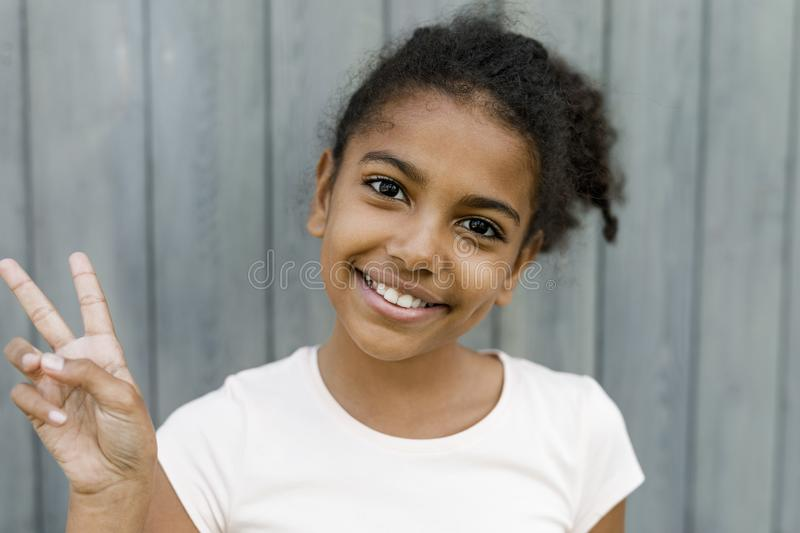 Close up portrait of smiling girl. Showing victory sign royalty free stock photos