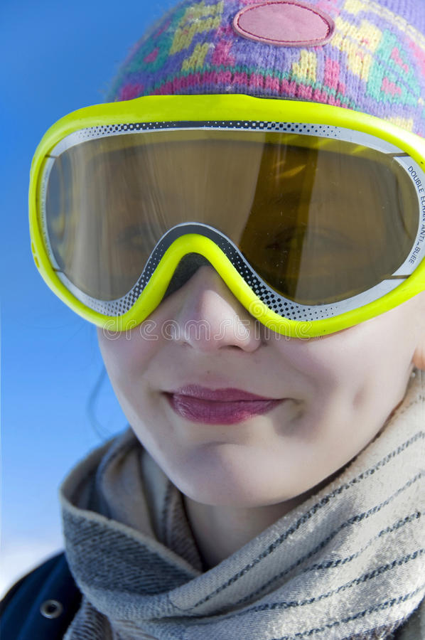 Close up portrait of a smiling girl with ski mask. Blue ski background stock photos