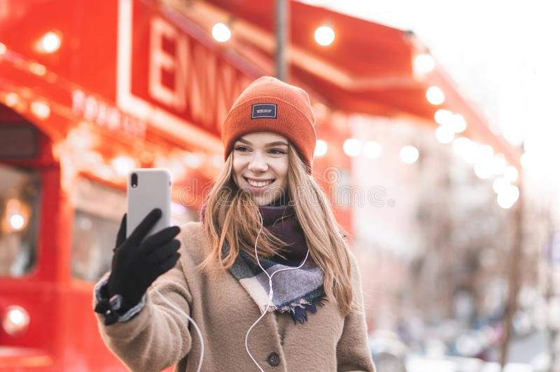Close-up portrait of a smiling girl in warm clothes takes selfie on a smartphone with a bright red city background. Beautiful girl royalty free stock photo