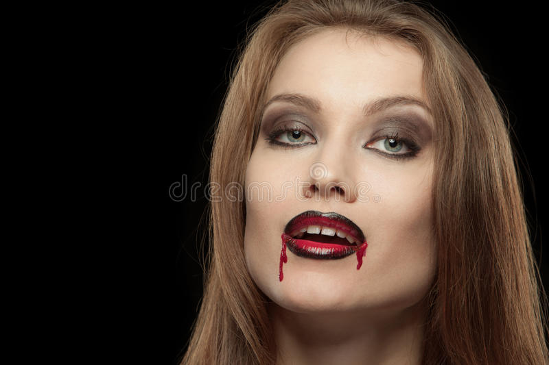 Close-up portrait of a smiling gothic vampire. Woman on a black background stock photo